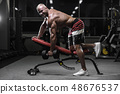 Handsome strong bodybuilder athletic men pumping 48676537