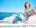 Summer vacation - young woman driving a motor boat 48677795