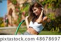 Beautiful young woman having fun in summer garden 48678697