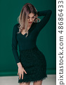 blonde woman posing in green dress on green background 48686433