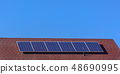 Solar panels on a red roof beneath clear blue sky 48690995
