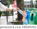 Woman hand throwing empty plastic to a bin 48696481