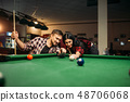 Couple plays in billiard room, male player aiming 48706068