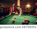 Family couple plays in billiard room 48706091