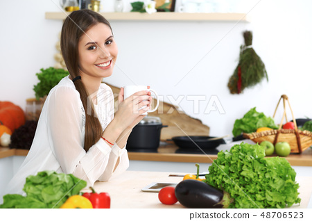 Young happy woman is holding white cup and looking at the camera while sitting at wooden table in 48706523