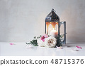 Vintage silver Moroccan, Arabic lantern with glowing candle, green branches, rose flowers and pink 48715376