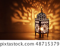 Silhouette of Moroccan ornamental lantern with burning glowing candle. Decorative shadows. Festive 48715379