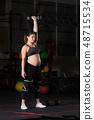 Pregnant female athlete doing dumbbell power snatch 48715534