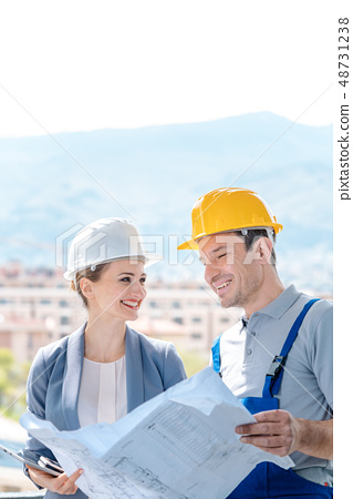 Principal and builder reading blueprints on construction site 48731238