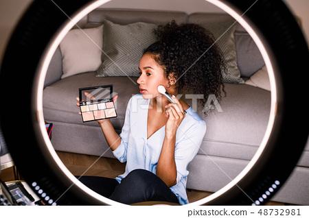 Woman beauty vlogger recording a makeup tutorial  48732981