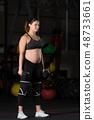 Pregnant female athlete doing dumbbell power snatch 48733661