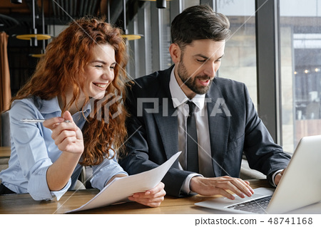 Businesspeople having business lunch at restaurant sitting browsing laptop laughing 48741168