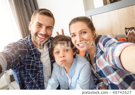 Family at home sitting on couch in living room together taking selfie pictures parents making horns 48742627