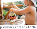 A midsection of small girl with a drink standing by a table on a patio in summer. 48742782