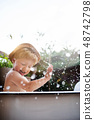 Small boy with a hat in bath outdoors in garden in summer, playing in water. 48742798