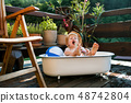 Small boy with a hat in bath outdoors in garden in summer, playing in water. 48742804