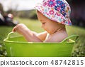 Small girl with a hat in bucket outdoors in garden in summer, playing in water. 48742815