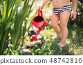 Small boy with can outdoors in garden in summer, watering flowers. A midsection. 48742816