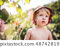 Small boy with a hat standing outdoors in garden in summer. Copy space. 48742819