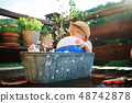Small boy with a ball in bath outdoors in garden in summer, playing in water. 48742878