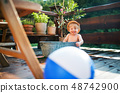 Small boy with a ball in bath outdoors in garden in summer, playing in water. 48742900
