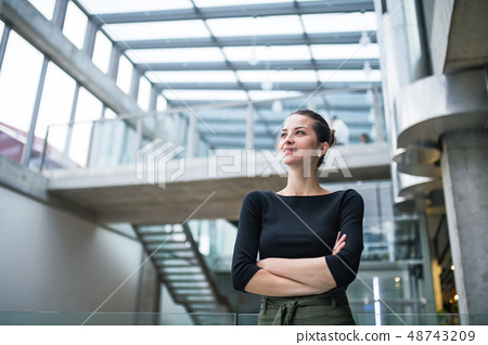 A portrait of young businesswoman standing in corridor outside office, arms crossed. 48743209