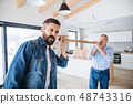 Two men having fun when furnishing new house, a new home concept. 48743316