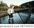 A small toddler boy standing in water and holding a net by a lake, fishing. 48744033