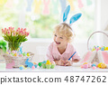 Kids on Easter egg hunt. Children dye eggs. 48747262