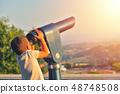 Little boy looking into tourist telescope 48748508