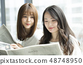 Two women reading a newspaper on the window side 48748950