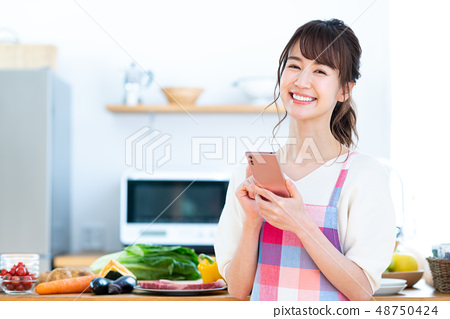 Young woman (smart phone kitchen) 48750424