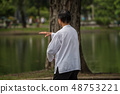 Man exercising by Tai Chi in a outdoor park 48753221