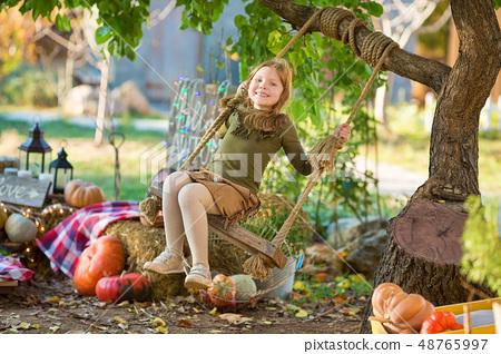 happy child girl with pumpkin outdoors halloween 48765997