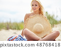Naked woman on the beach holding summer  hat 48768418