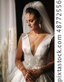 Portrait of beautiful bride at home. Woman stand by the window in wedding dress 48772556