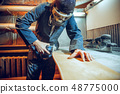 Carpenter using circular saw for cutting wooden boards. 48775000