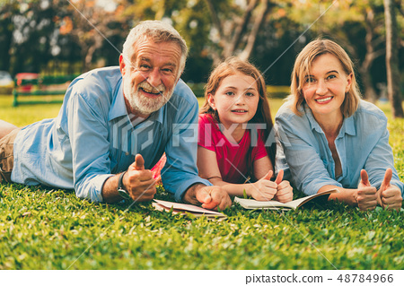 Happy family read books together in park garden. 48784966