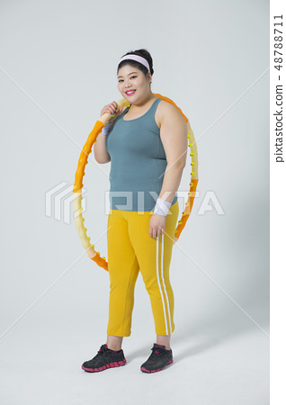 Large girl eating healthy foods and exercise for weight loss, diet concept isolated on gray background 254 48788711