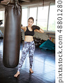 Young beautiful woman punching A Bag With Boxing Gloves On 48801280
