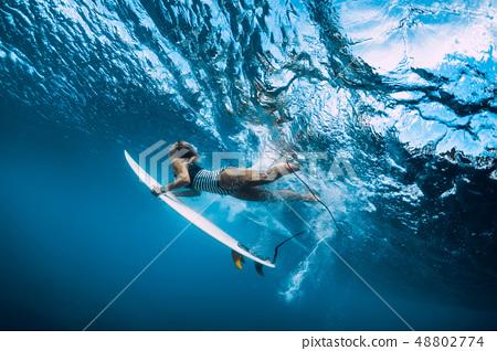 Surfer woman dive underwater under wave 48802774