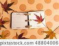 Small notebook and autumn leafs on a table 48804006