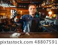 Male bartender tasting beverage at the bar counter 48807591
