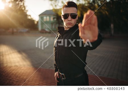 Serious police officer shows a hand stop sign 48808143