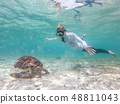 Woman on vacations wearing snokeling mask swimming with sea turtle in turquoise blue water of Gili 48811043