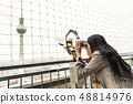Girl looks at Berlin TV tower from binoculars 48814976