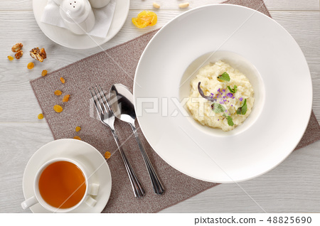 rice porridge in a white plate on a white wooden background 48825690