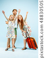 Happy parent with daughter and suitcase at studio isolated on blue background 48830505