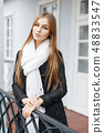 Beautiful girl in a white knitted scarf  48833547