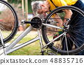 Man maintaining his bicycle for the new season 48835716